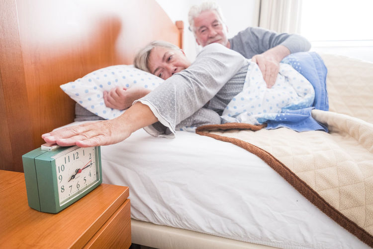 Senior Woman Closing Alarm Clock While Lying By Man On Bed