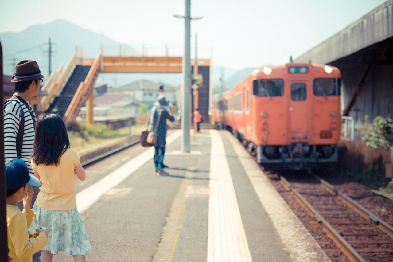 Father with children looking at train arriving at railroad platform