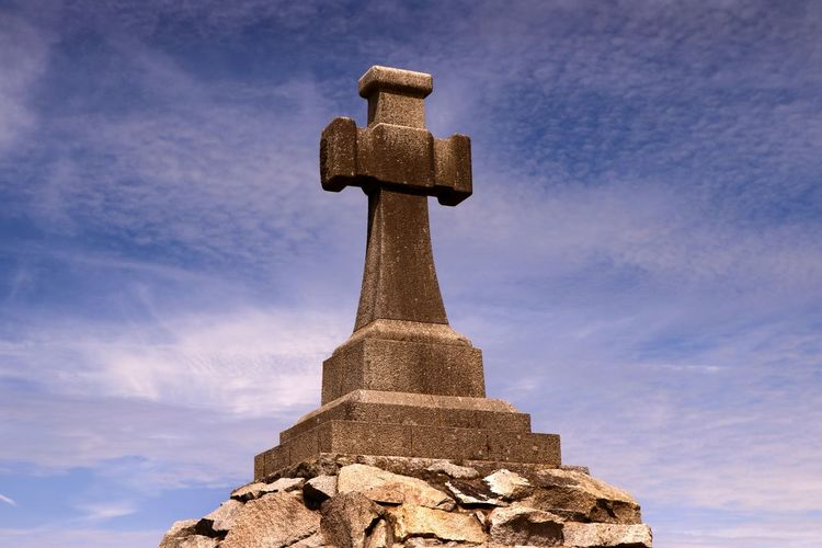 A stone cross stands on a rocky platform on the clifftop near Newquay in Cornwall England Stone Cross Travel Travel Photography Architecture Cloud - Sky Cross Crusifix Day Monument No People Outdoors Religion Sky Spirituality Symbolic  Tourist Destination Travel Destination
