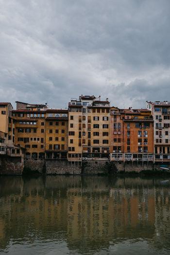 River by buildings against sky