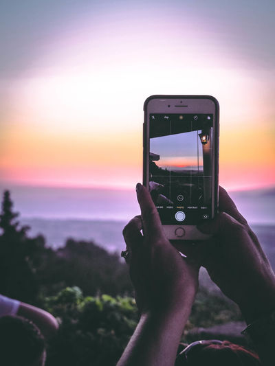 Activity Communication Focus On Foreground Hand Holding Horizon Over Water Human Hand Mobile Phone Nature One Person Outdoors Photographing Photography Themes Portable Information Device Real People Screen Sky Smart Phone Sun Sunset Technology Water Wireless Technology