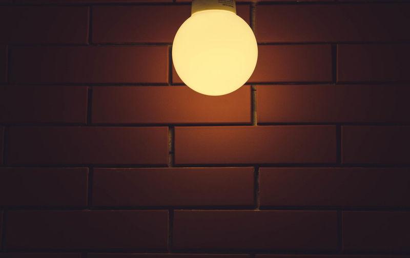 Illuminated Light Bulb Against Brick Wall