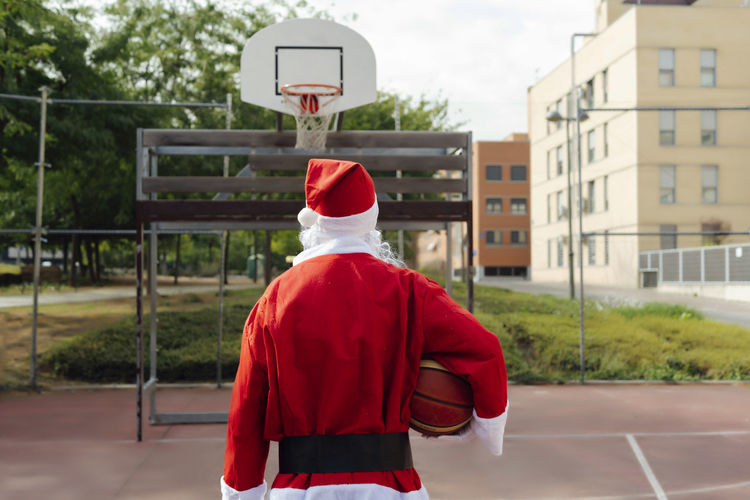 Rear view of man standing by basketball court