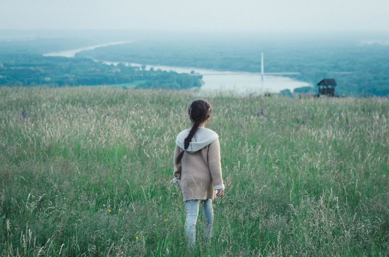 Rear view of girl looking at field