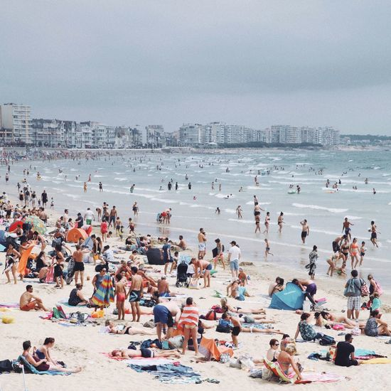People at beach against sky during summer