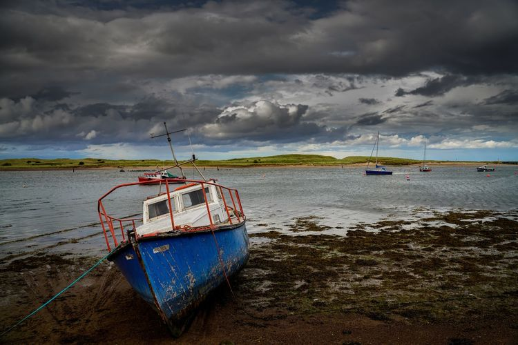 Boat moored on sea shore against sky