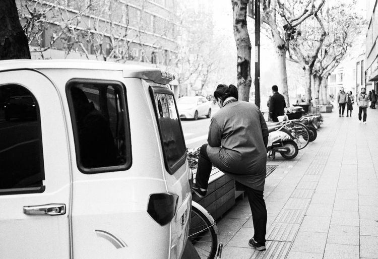 Mode Of Transportation City Transportation Car Motor Vehicle Street Land Vehicle Real People Incidental People Men Architecture Building Exterior Day People City Life Built Structure Tree Rear View Lifestyles Plant Outdoors Streetphotography Film Photography