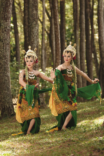 Women in traditional clothing dancing at forest