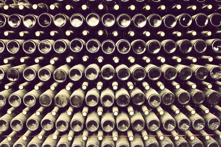 Full frame shot of old wine bottles on shelf