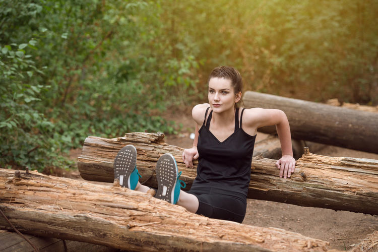 Full length of young woman sitting on log