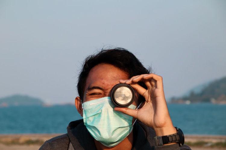 Portrait of man holding sunglasses against sea