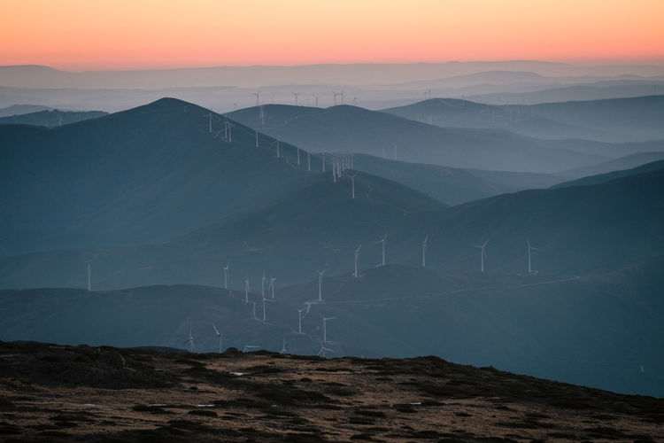 High angle view of windmills on mountains against sky during sunset