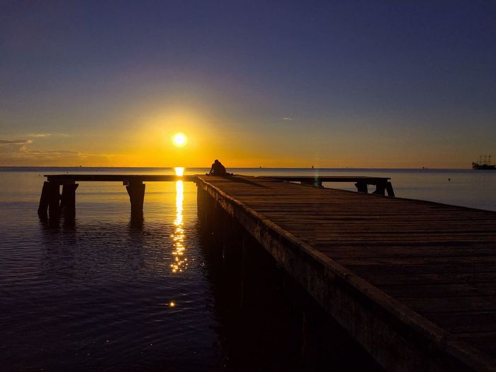 Silhouette pier over sea against clear sky during sunset