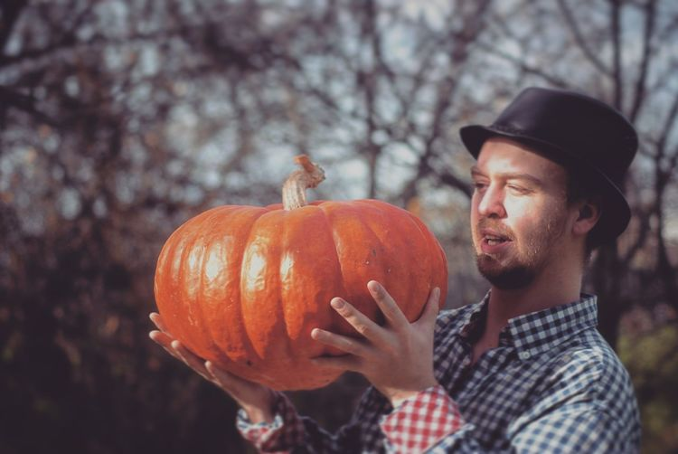 Young man holding pumpkin standing by tree outdoors