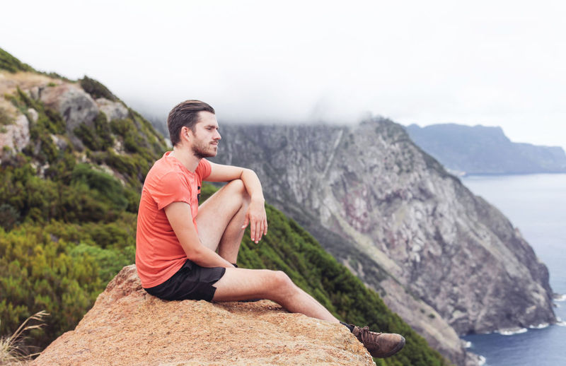 Man sitting on rock against mountains