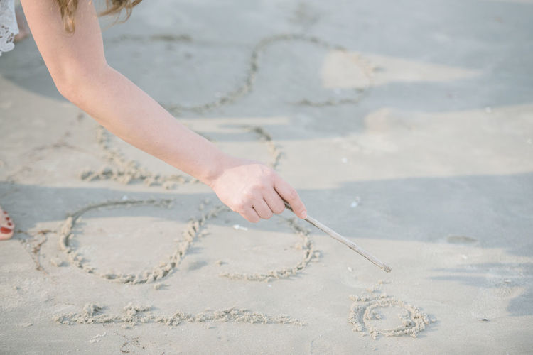 Close-up of woman writing on sand at beach