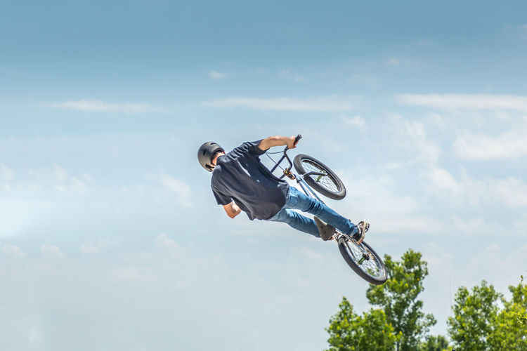 Low angle view of man performing stunt on bicycle against sky