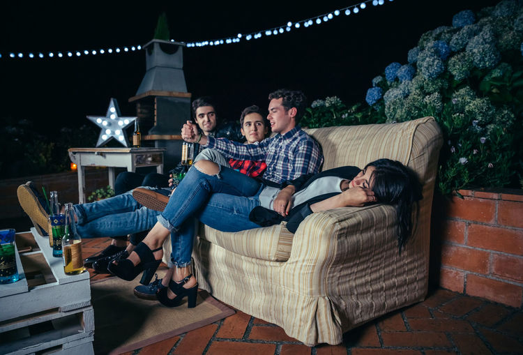 Woman sleeping with male friends talking on sofa at patio during night