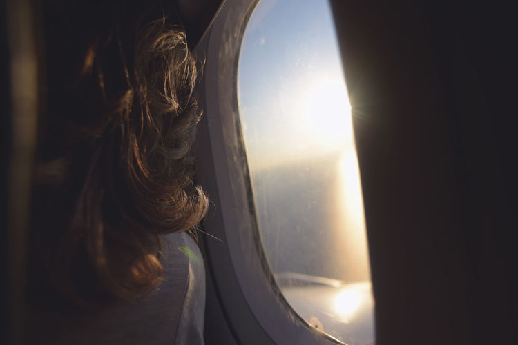Rear view of woman looking through airplane window