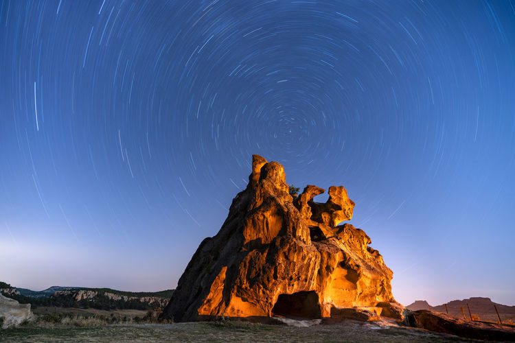 Rock formations against star trail at night