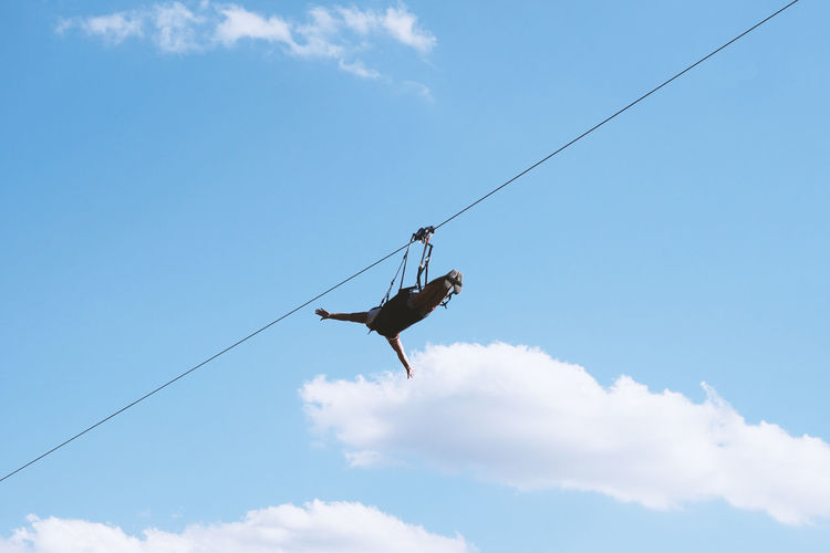 Low angle view of person hanging on rope against blue sky