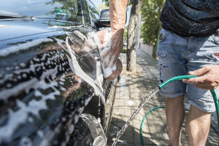 Wash Car Washing Car Wash Close Up Men Foam Hose One Person Real People Day Water Holding Casual Clothing Human Body Part Lifestyles Nature Human Hand Standing Mode Of Transportation Hand Outdoors Leisure Activity Spraying Garden Hose Flowing Water