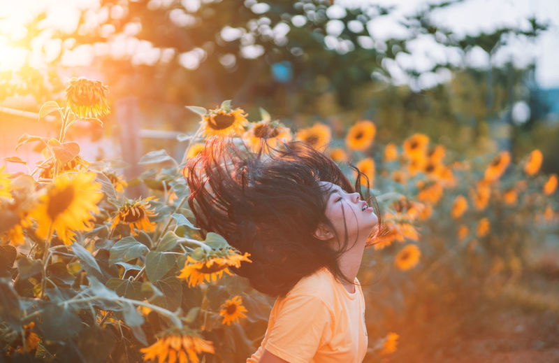 Girl flicking hair Sunflower in the evening with orange light. Wherever life plants you bloom with grace. 🌻 🌻 🌻 Blooming Women Nautical Vessel Nature Photography Nature_collection Celebration Vintage Holiday Life Light Light And Shadow Sunflower🌻 Sunflowers🌻 Sunflowers Sunrise Sunlight Sunset Sun Bokeh Lights Bokehlicious Bokeh Photography Bokeh Flower Collection Flowers Flower Head Hairstyle Sunflower Outdoors Portrait Beauty In Nature Headshot Day Field Growth Land Focus On Foreground Side View Lifestyles Childhood Flowering Plant Flower Nature Real People Child Leisure Activity One Person Plant