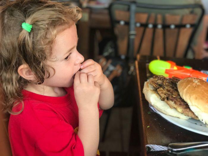 Side view of girl eating fresh hamburger at restaurant