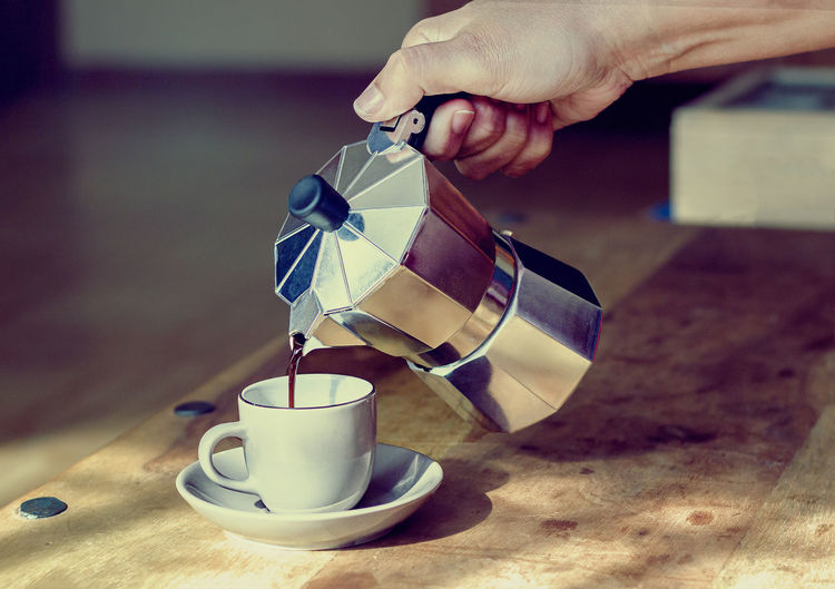 Woman's hand holding coffee maker while pouring coffee on cup Close-up Coffee - Drink Coffee Cup Coffee Pot Cup Drink Espresso Espresso Maker Food And Drink Indoors