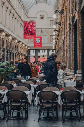 People at sidewalk cafe against buildings in city