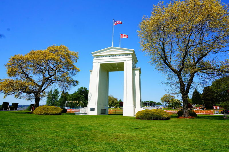 Peace Arch Architecture Autumn Building Exterior Built Structure Clear Sky Day Flag Grass Green Color History Maple Leaf Memorial Nature No People Outdoors Patriotism Peace Arch Canadian Border Sky Tree
