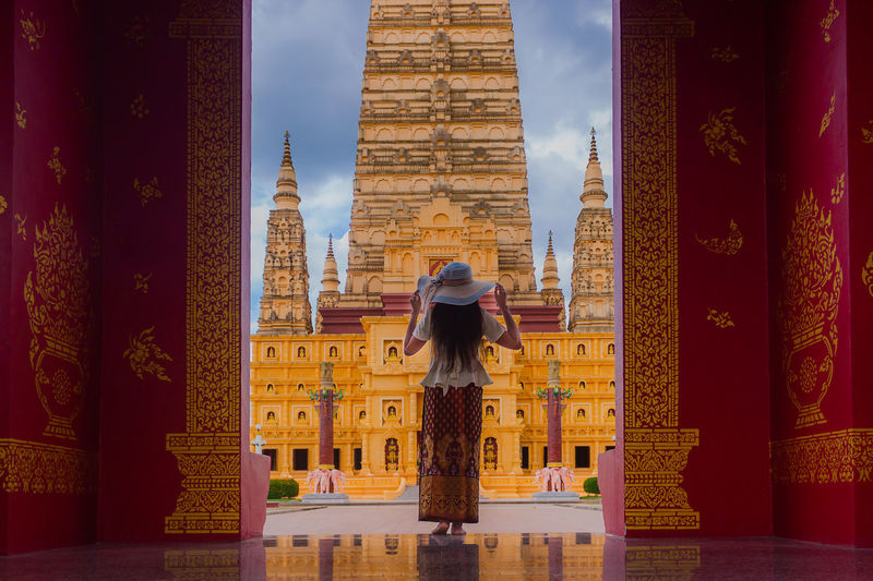 Rear view of woman wearing hat standing against religious building