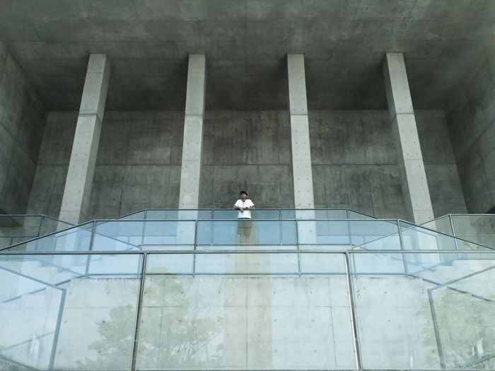 Low angle view of teenage boy leaning on railing in incomplete building
