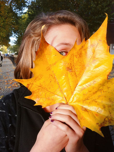 Low section of woman standing on yellow maple leaf during autumn