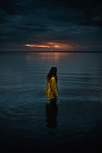 Woman standing on sea against sky during sunset