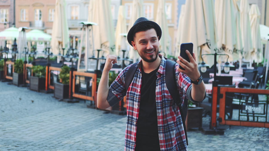 Portrait of smiling young man holding smart phone while standing outdoors