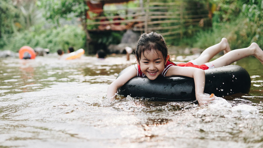Happy girl relaxing on inflatable ring floating in lake