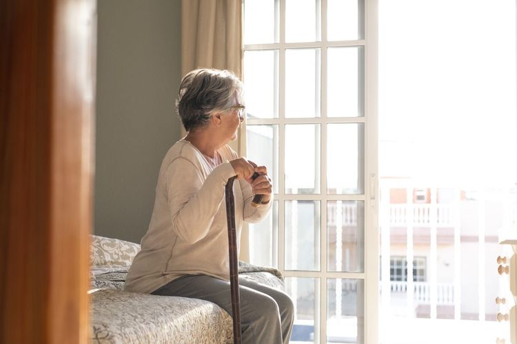 Woman looking at camera while sitting in window