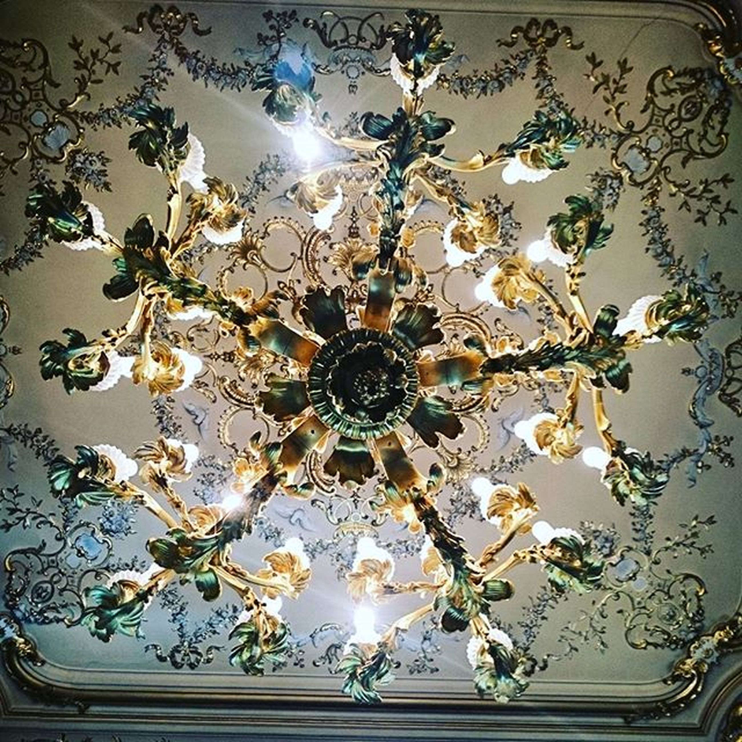 indoors, ceiling, chandelier, decoration, hanging, lighting equipment, illuminated, decor, home interior, low angle view, ornate, electric lamp, floral pattern, table, luxury, design, vase, still life, electricity, no people