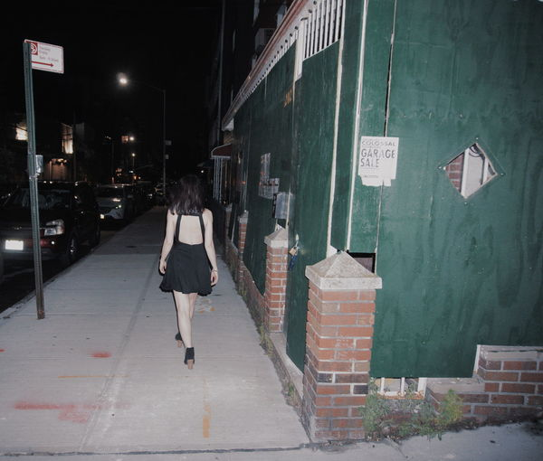 Rear view of woman walking on footpath amidst buildings in city alone at night