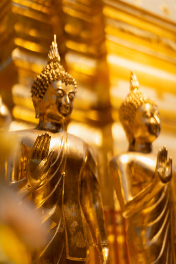 hand of golden buddha statue whith blurred golden pagoda background, selective focus, buddhist holy day concept Asian  Bright Buddha Buddhism Buddhist Ceremony Culture Day Focus Golden Hand Holy Monk  Pagoda Religion Selective Statue Symbol Temple Thai Thailand Yellow