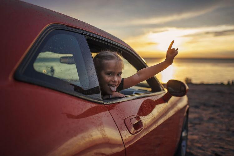 Portrait of girl looking through car window