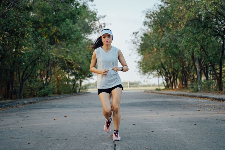 Woman runner does jogging on the city road. Sport and workout. Sport Workout Jogging Running Exercise One Person Road Real People Plant Full Length Lifestyles Front View Tree Casual Clothing Day Transportation Young Adult Leisure Activity Exercising Young Women Women Outdoors Shorts