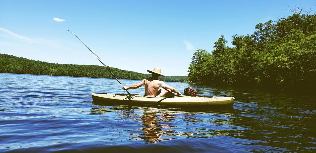Rear view of shirtless man fishing in boat against sky