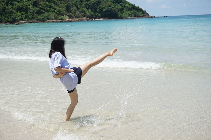 Woman kicking water while standing at beach
