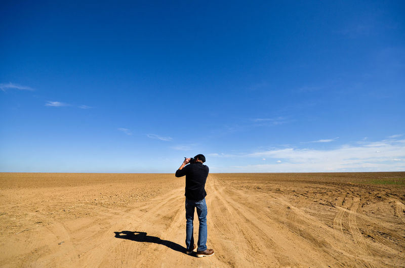 Rear view of man photographing on landscape against blue sky