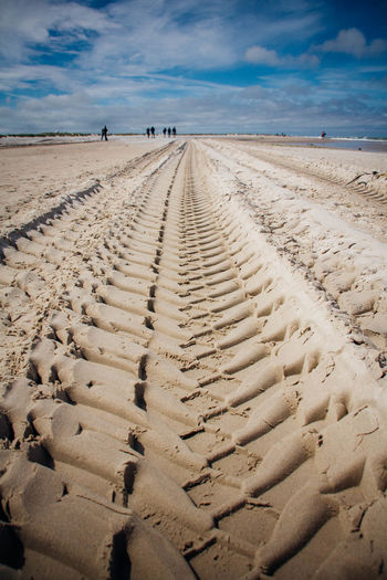 Surface level of tire tracks on sand at beach against sky