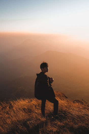 Man standing on cliff against sky during sunset