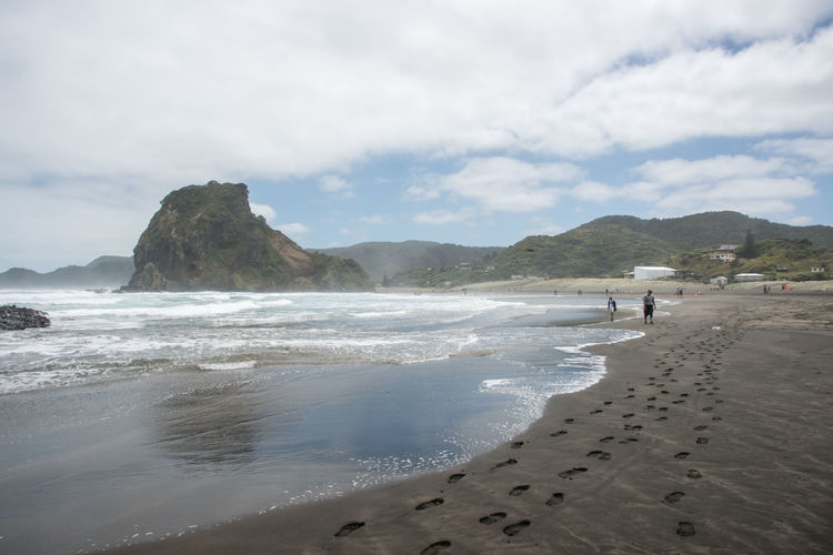 Auckland, New Zealand-December 17,2016: Tourists at Piha Beach with volcanic black sand in Auckland, New Zealand Auckland Lion Rock Tasman Sea Tourist Tourist Attraction  Beach Beauty In Nature Black Eroded Land Motion Mountain Nature New Zealand Piha Sand Scenics - Nature Sea Sky Tourism Tranquil Scene Volcanic Landscape Volcano Water Wave