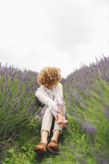 Woman Sitting On Lavender Field Against Sky